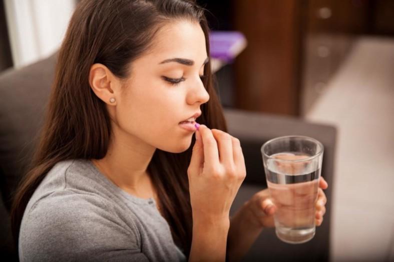Девушка пьет витамин